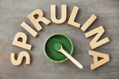 Composition with wooden letters and bowl with spirulina. Powder on table stock images