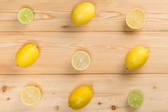 Composition on a wooden light background of lobules and whole lemons stock photo