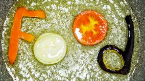 Composition of the word food in a frying pan made from vegetables. Letters from vegetables form the word food in a frying pan stock footage