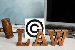 Composition with word LAW, gavel and copyright symbol. On table stock photos