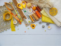 Composition of yellow accessories for needlework on wooden background. Knitting, embroidery, sewing. Small business. Income from h Royalty Free Stock Photography