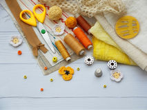 Composition of yellow accessories for needlework on wooden background. Knitting, embroidery, sewing. Small business. Income from h Royalty Free Stock Photo