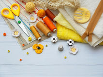 Composition of yellow accessories for needlework on wooden background. Knitting, embroidery, sewing. Small business. Income from h Royalty Free Stock Photos