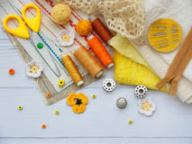 Composition of yellow accessories for needlework on wooden background. Knitting, embroidery, sewing. Small business. Income from h. Obby Stock Image