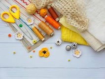 Composition of yellow accessories for needlework on wooden background. Knitting, embroidery, sewing. Small business. Income from h Stock Photos