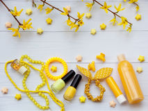 Composition of  yellow accessories for young girl or teenager. Nail polishes, lipstick, hair clips, bands, beads, bracelet, perfum Stock Photos
