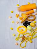 Composition of  yellow accessories for young girl or teenager. Nail polishes, lipstick, hair clips, bands, beads, bracelet, perfum Royalty Free Stock Images