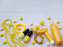 Composition of  yellow accessories for young girl or teenager. Nail polishes, lipstick, hair clips, bands, beads, bracelet, perfum Royalty Free Stock Photography