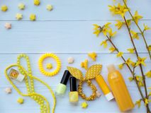 Composition of  yellow accessories for young girl or teenager. Nail polishes, lipstick, hair clips, bands, beads, bracelet, perfum Stock Photo