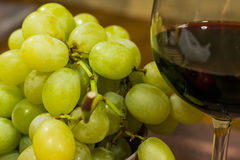 Composition of yellow muscat grape and glass of red wine - close up Royalty Free Stock Images