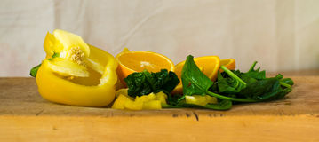 Composition of yellow pepper, slices of orange and spinach Stock Images