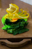 Composition of yellow pepper, slices of orange and spinach Stock Photos