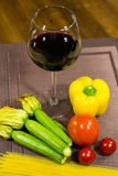 Composition of yellow pepperoni, glass of wine, courgettes, tomatoes and pasta on a wooden board Royalty Free Stock Photos