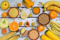 Composition of yellow vegetables, beans and fruits - banana, corn, lemon, plum, apricot, pepper, zucchini, tomato, asparagus bean, Royalty Free Stock Photography