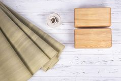 Composition of yoga, meditation or pilates accessories on white background with copy space. Top view of green yoga mat, two wooden blocks and white belt on royalty free stock images