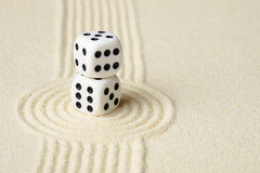 Composition on Zen garden - sand, and two dice Royalty Free Stock Photo