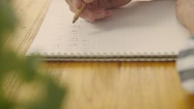 Compositor que escribe la notación musical en el cuaderno almacen de metraje de vídeo