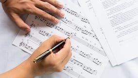 Compositore di canzone che lavora alla carta per appunti di musica fotografia stock