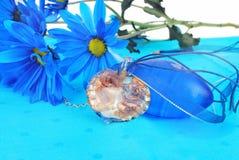 Composizione blu con il pendente del cuore. Fotografia Stock