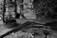 Composizione in caccia con il vecchi fucile, lampada e bicchiere di vino Immagini Stock Libere da Diritti