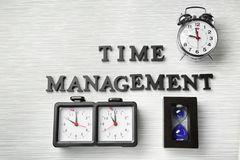 Composizione con differenti orologi e frase \ «gestione di tempo \» sulla tavola immagine stock