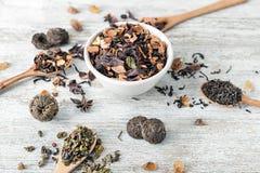 Composizione con differenti tipi di tè asciutti su fondo di legno fotografia stock