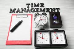 Composizione con gli orologi, la lavagna per appunti e la frase \ «la gestione di tempo differenti \» sulla tavola immagini stock