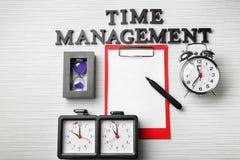 Composizione con gli orologi, la lavagna per appunti e la frase \ «la gestione di tempo differenti \» sulla tavola fotografia stock libera da diritti