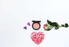 Composizione con i cosmetici ed i fiori di trucco su fondo bianco Immagine Stock