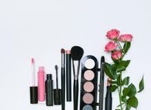 Composizione con i cosmetici, le spazzole, gli shadoes ed i fiori di trucco su fondo bianco Immagini Stock Libere da Diritti