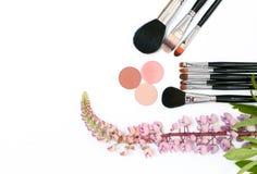 Composizione con i cosmetici, le spazzole, gli shadoes ed i fiori di trucco su fondo bianco Fotografia Stock Libera da Diritti