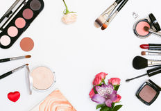 Composizione con i cosmetici, le spazzole, gli shadoes ed i fiori di trucco su fondo bianco Fotografie Stock Libere da Diritti