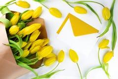 Composizione con i fiori gialli freschi, i petali e la busta gialla aperta su fondo bianco Disposizione piana, vista superiore Pr immagine stock libera da diritti