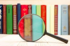 Composizione con i libri e la lente d'ingrandimento della libro con copertina rigida sulla tavola Di nuovo alla scuola, copi lo s Fotografia Stock