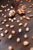 Composizione con i pistacchi e le mandorle sui cucchiai di legno d'annata Fotografia Stock