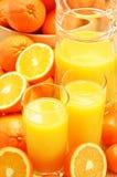 Composizione con i vetri di succo d'arancia e dei frutti Immagine Stock