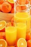 Composizione con i vetri di succo d'arancia e dei frutti Fotografia Stock