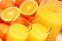 Composizione con i vetri di succo d'arancia e dei frutti Immagini Stock