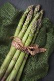 Composizione con il gruppo legato dell'asparago sulla pietra scura Fotografia Stock