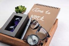 Composizione con il taccuino, gli orologi ed i vetri sulla tavola Concetto della gestione di tempo immagine stock