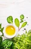 Composizione con l'insalata e la ciotola verdi dell'erba con olio Immagini Stock