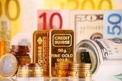 Composizione con la barra, le banconote e le monete di oro da 50 grammi Fotografia Stock