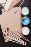 Composizione con la carta, le pitture e le spazzole del mestiere sulla tavola nera Immagine Stock