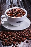 Composizione con la tazza dei chicchi di caffè di Nescafe Immagini Stock