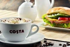 Composizione con la tazza del caffè e del panino di Costa Coffee fotografie stock