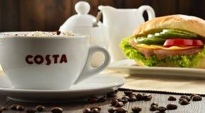 Composizione con la tazza del caffè e del panino di Costa Coffee fotografia stock