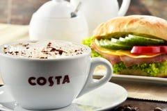 Composizione con la tazza del caffè e del panino di Costa Coffee immagine stock libera da diritti