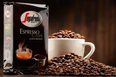Composizione con la tazza ed i fagioli del caffè di Segafredo Zanetti Immagini Stock Libere da Diritti