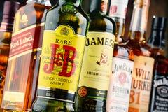 Composizione con le bottiglie delle marche popolari del whiskey Fotografie Stock