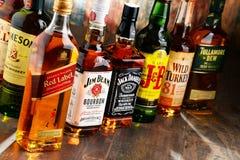 Composizione con le bottiglie delle marche popolari del whiskey Immagine Stock